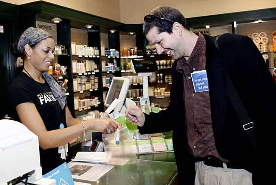 Airline passenger John Barrera (right) buys a plastic bag from Victoria Trapp at the Body Shop in the Atlanta airport Wednesday. Associated Press photo by Wilford A. Harewood