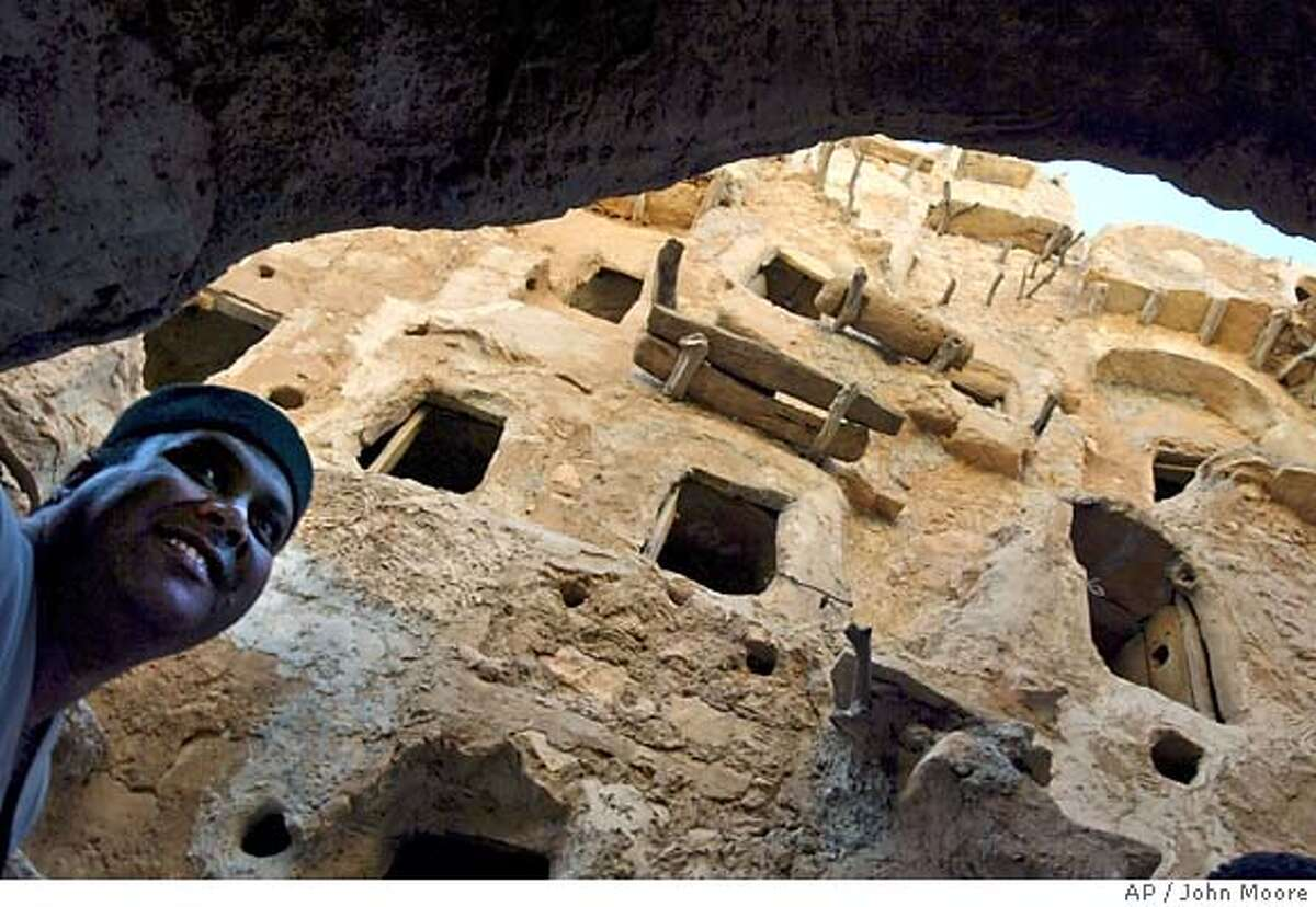 TRAVEL **FOR IMMEDIATE RELEASE** A guide shows an ancient castle in Nalut in western Libya Feb. 3, 2004. Built into a rocky peak, the 800-year-old castle features seven stories of caves where people stored food to protect it from raiding enemies.(AP Photo/John Moore) FOR IMMEDIATE RELEASE.