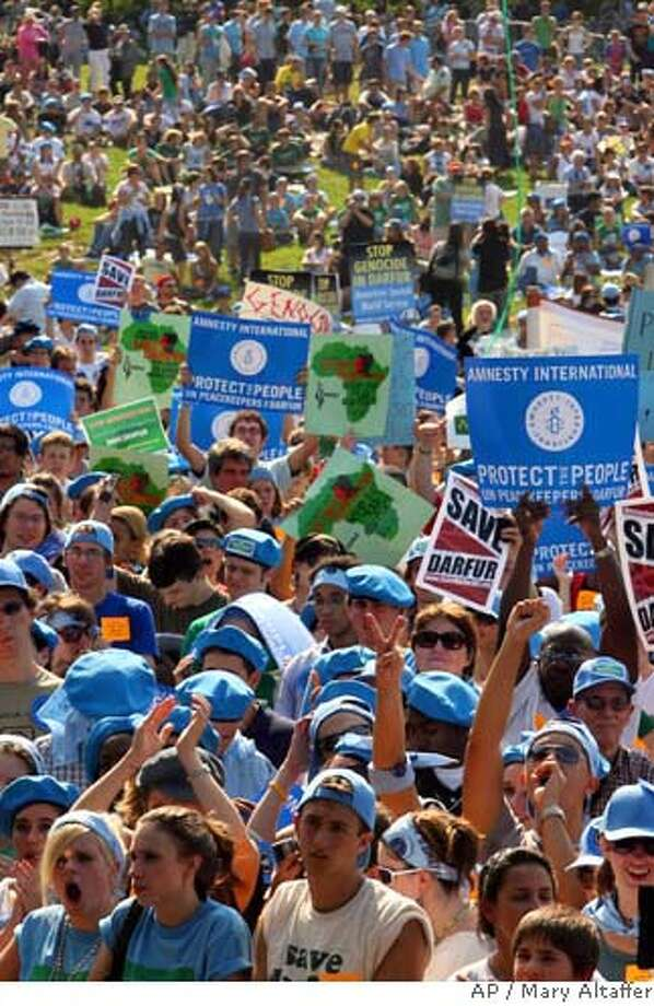 Demonstrators shouts slogans, hold up their fists and make peace signs during a Save Darfur Coalition rally in New York's Central Park, Sunday, Sept. 17, 2006. Demonstrator called on the United Nations peacekeeping force to be immediately deployed to the Darfur region to stop the genocide. (AP Photo/Mary Altaffer) Photo: MARY ALTAFFER
