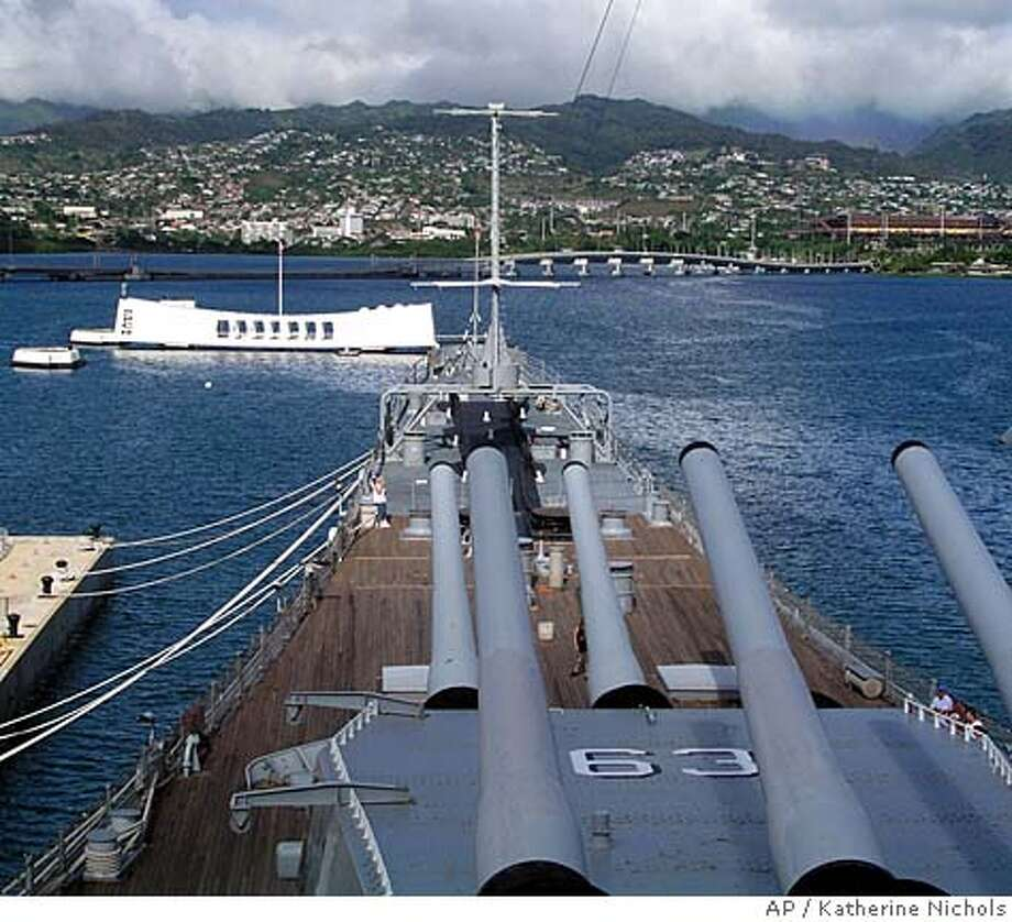 TRAVEL HAWAII Pearl Harbor -- The Battleship Missouri's massive turrets are shown pointing toward the Arizona Memorial at Pearl Harbor, Hawaii, in this undated photo. (AP Photo/Katherine Nichols) Ran on: 03-20-2005  Officer of the deck: Volunteer Ben Davis, under the famous 16-inch, 50-caliber gun turrets, greets visitors to the Missouri, which is anchored bow to bow with the Arizona in Pearl Harbor. Photo: KATHERINE NICHOLS