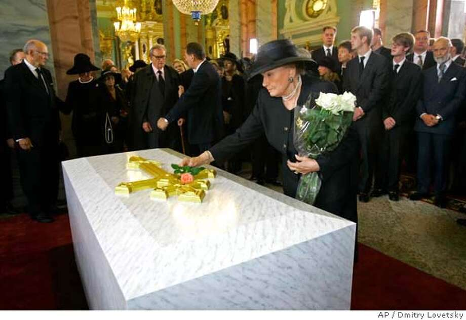 An unidentified member of the Romanov family lays flowers onto the tomb of Czarina Maria Feodorovna during a burial ceremony in the royal crypt at the Cathedral of the Peter and Paul Fortress in St. Petersburg, Russia, Thursday, Sept. 28, 2006. Russian Orthodox Patriarch Alexy II on Thursday led burial ceremonies for Czarina Maria Feodorovna, the Danish-born empress whose remains are to be interred in her adopted land 78 years after her death. Maria Feodorovna was the mother of Russia's last czar, Nicholas II, who was executed by the Bolsheviks in 1918. She went into exile in Denmark in 1919 and died in 1928. (AP Photo/Dmitry Lovetsky, Pool) Photo: DMITRY LOVETSKY