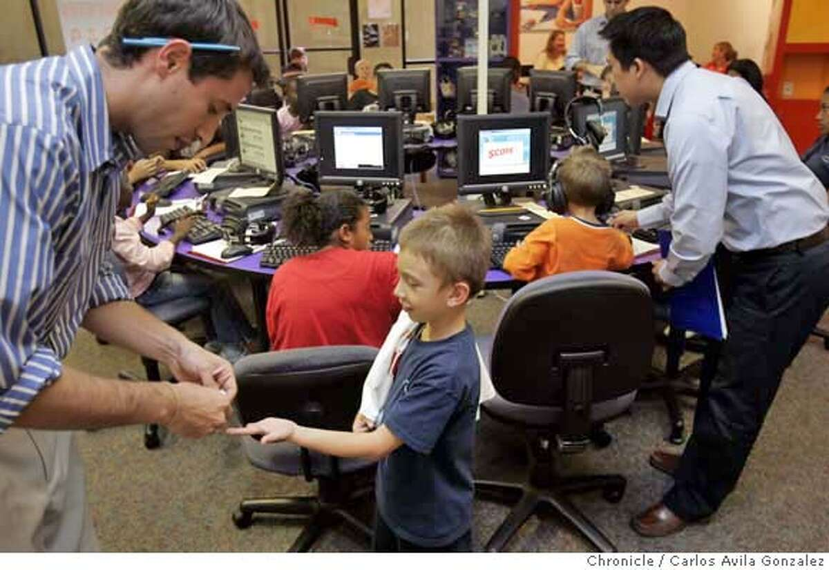 .JPG Dylan Goode, 6, gets a reward from Jason Angress, Score! Center Director, after Dylan completed an exercise at the center on Tuesday, September 26, 2006. Brothers Dylan and Matthew Goode bounded into the Score! Educational Center in Alameda, a room full of computers and little else. They settled in front of computer screens and slid on headphones for their animated math and phonics sessions. The academic push is starting well before kindergarten these days as parents who are worried about the rigours of elementary school enroll their tots in a new slew of tutoring programs and computer-and-math centered preschools or sit them in front of videos that promise to teach children as young as 15 months their letters, numbers and shapes in a few short weeks. Photo by Carlos Avila Gonzalez/The San Francisco Chronicle Photo taken on 9/26/06, in Alameda, Ca, USA **All names cq (source) MANDATORY CREDIT FOR PHOTOG AND SAN FRANCISCO CHRONICLE/ -MAGS OUT