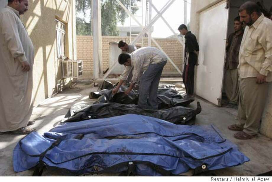 Residents identify the bodies of some of the eight people killed during a U.S. raid and air strike in Baquba, 65 km (40 miles) northeast of Baghdad, September 27, 2006. A U.S. raid and air strike on Wednesday killed eight people, including seven members of one family, and wounded two others in the town of Baquba, the U.S. military and police said. The U.S. said the four men in the family of seven were suspected militants with links to al Qaeda. REUTERS/Helmiy al-Azawi (IRAQ) 0 Photo: HELMIY AL AZAWI