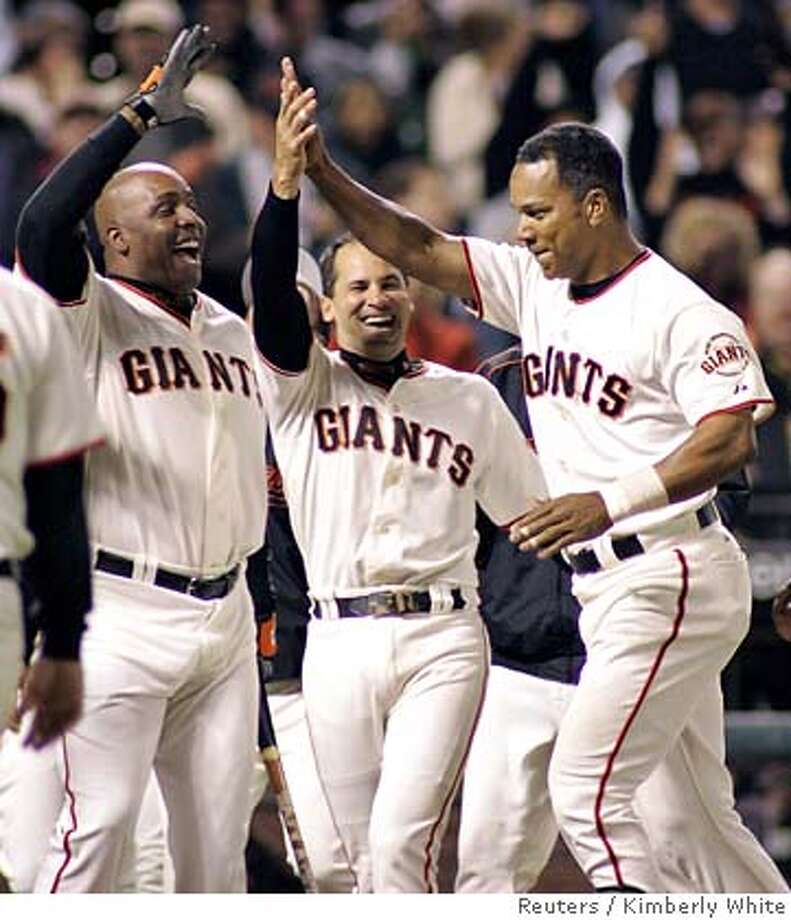 San Francisco Giants Moises Alou (R) is congratulated by his teammates Barry Bonds (L) and Omar Vizquel after hitting a two-run home run in the ninth inning to win their National League baseball game against the Arizona Diamondbacks in San Francisco, California, September 26, 2006. REUTERS/Kimberly White (UNITED STATES) Photo: KIMBERLY WHITE