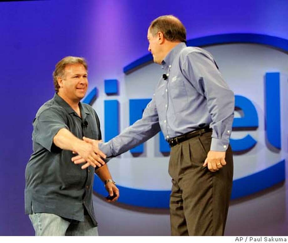 Intel Corp. CEO Paul Otellini, right, ishakes hands with Phil Schiller, left, Apple Senior Vice President of Worldwide Product Marketing, at the Intel Developer Forum in San Francisco, Tuesday, Sept. 26, 2006. Otellini emphasized the energy efficiency of his company's latest microprocessors at the chip maker's developer conference. (AP Photo/Paul Sakuma) Photo: PAUL SAKUMA