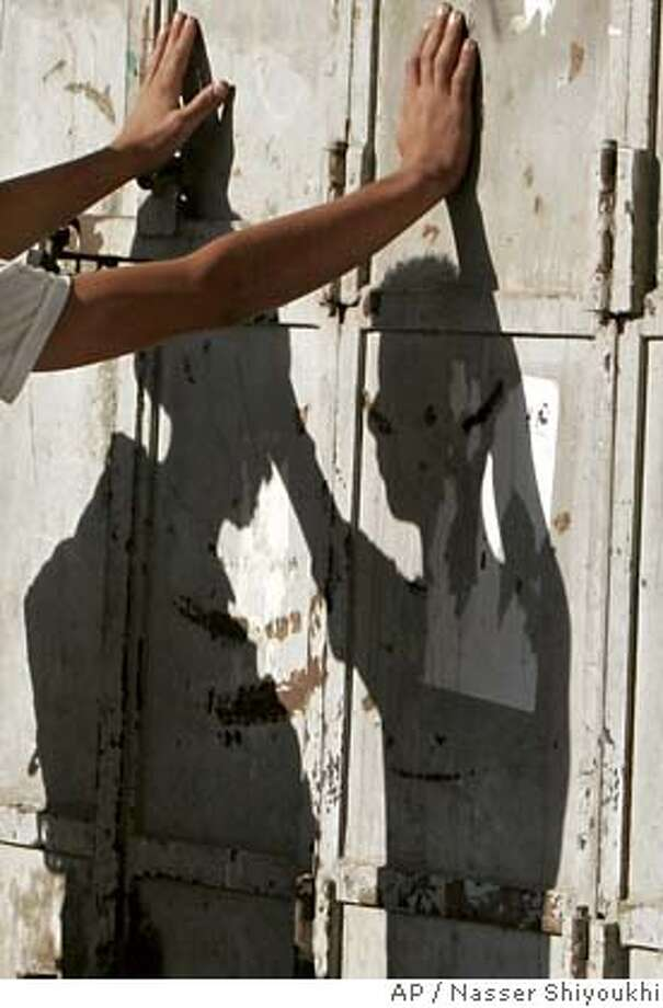 The shadows of an Israeli soldier, left, and a Palestinian man are cast onto a wall as the man is searched at a checkpoint in the West Bank city of Hebron, Tuesday, Sept. 26, 2006. (AP Photo/Nasser Shiyoukhi) Photo: NASSER SHIYOUKHI
