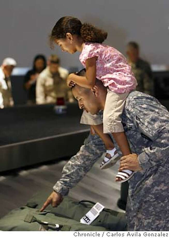 RETURN27_021_CAG.JPG  Maj. Paul Monroe and his daughter, Maya, 6, of Oakland, Ca., look for his bags at baggage claim at the Oakland Airport. Soldiers from the California National Guard's 49TH Military Police Brigade arrived at Oakland International Airport on Tuesday, September 26, 2006, and were greeted by family and friends following a year-long deployment to Camp Victory in Baghdad, Iraq.  Photo by Carlos Avila Gonzalez/The San Francisco Chronicle  Photo taken on 9/26/06, in Oakland, Ca, USA  **All names cq (source) MANDATORY CREDIT FOR PHOTOG AND SAN FRANCISCO CHRONICLE/ -MAGS OUT Photo: Carlos Avila Gonzalez