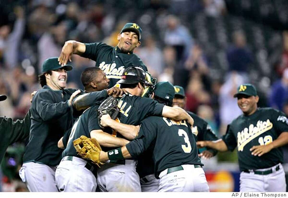 Oakland Athletics pile on after clinching the AL West division title by beating the Seattle Mariners in a baseball game Tuesday, Sept. 26, 2006, in Seattle. The Athletics won 12-3.(AP Photo/Elaine Thompson)