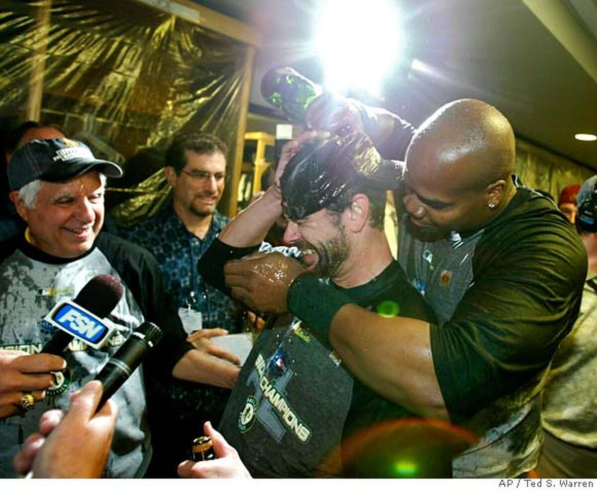 Oakland Athletics' Frank Thomas, right, dumps champagne on teammate Jason Kendall during a TV interview in the clubhouse after Oakland beat the Seattle Mariners 12-3 to clinch the AL West division Tuesday, Sept. 26, 2006, at Safeco Field in Seattle. At left is A's owner Lewis Wolff. (AP Photo/Ted S. Warren)