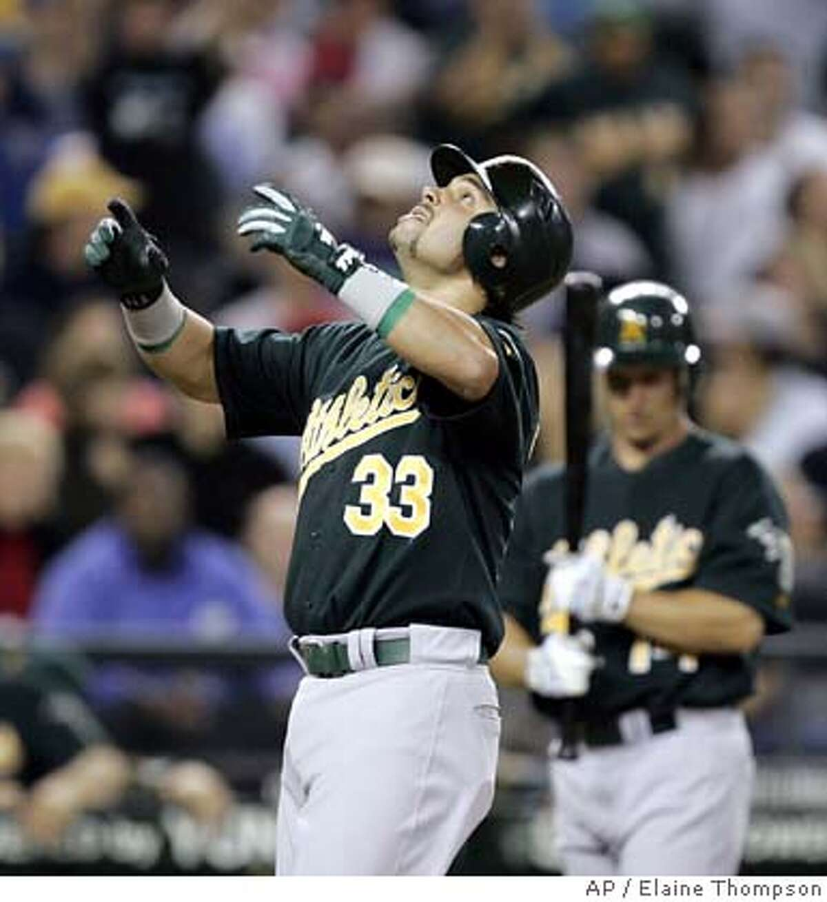 Oakland Athletics' Nick Swisher begins to raise his arms to point skyward as he crosses home on his second inning home run against the Seattle Mariners Tuesday, Sept. 26, 2006, in Seattle. Waiting on-deck is Mark Ellis. (AP Photo/Elaine Thompson)