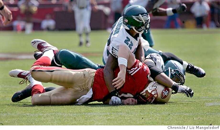 49ers QB Alex Smith (#11) is pushed into the turf in the 1st quarter by Eagles Joselio Hanson(22) and Eagles Juqua Thomas.(75) The San Francisco niners play the Philadelphia Eagles at Monster Park in San Francisco on Sept. 24th, 2006.  Liz Mangelsdorf /The Chronicle MANDATORY CREDIT FOR PHOTOG AND SF CHRONICLE/ -MAGS OUT Photo: Liz Mangelsdorf