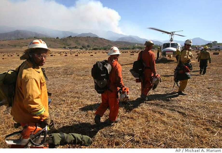 A hand crew prepares to board a helicopter Sunday, Sept. 24, 2006 near Ojai, Calif. to be dropped in to reinforce fire breaks at the Day Fire, seen in background. A blaze started by embers from the huge Day Fire burned about 7,000 acres in the canyons above Thomas Aquinas College in Santa Paula, which sits between Ojai and Fillmore along Highway 150, about 75 miles north of Los Angeles. The campus was evacuated late Saturday. (AP Photo/Michael A. Mariant) Photo: MICHAEL A. MARIANT