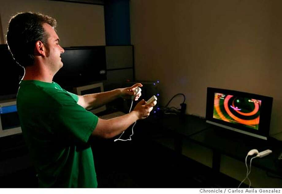 SEGA25_075_CAG.JPG  Ryan Jones, assistant lead tester at Sega, tries out the Wii Remote and Nunchuk controller at the Sega headquarters in San Francisco, Ca., on Thursday, September 21, 2006. Sega is one of the main developers working up games for the new Nintendo Wii, which uses innovative motion-sensing technology called the Wii Remote and Nanchuk to create a more immersive and engaging game experience. Many think this could be what opens up gaming to a much largeR audience, pushing it far into the mainstream.  Photo by Carlos Avila Gonzalez/The San Francisco Chronicle  Photo taken on 9/21/06, in San Francisco, Ca, USA  **All names cq (source) MANDATORY CREDIT FOR PHOTOG AND SAN FRANCISCO CHRONICLE/ -MAGS OUT Photo: Carlos Avila Gonzalez