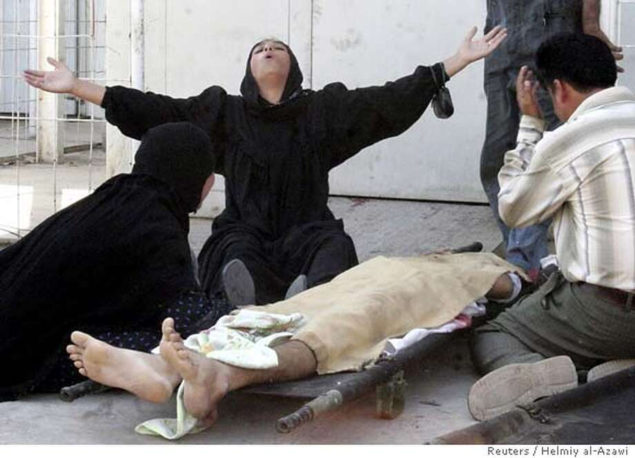 A woman and other relatives cry over the body of a man killed in Baquba, 65 km (40 miles) northeast of Baghdad, September 24, 2006. A policeman and a civilian were killed by gunmen in central Baquba, police and relatives said. REUTERS/Helmiy al-Azawi (IRAQ) 0 Photo: HELMIY AL AZAWI