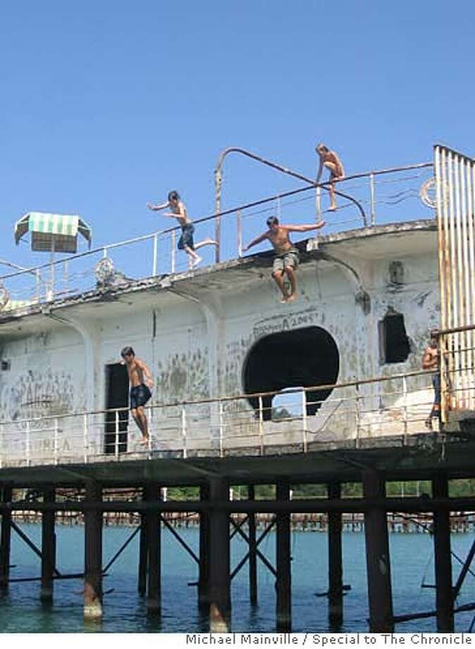 Local boys jumping off the abandoned ruins of the Amra cafe in Sukhumi. Photo by Michael Mainville/Special to The Chronicle  Ran on: 09-24-2006  Once a playground for Soviet elites, Abkhazia is now hurting. Boys, left, jump off the abandoned ruins of a cafe in Sukhumi, while a horse, above, grazes near a destroyed building on the Georgia border. Photo: Michael Mainville/Special To The