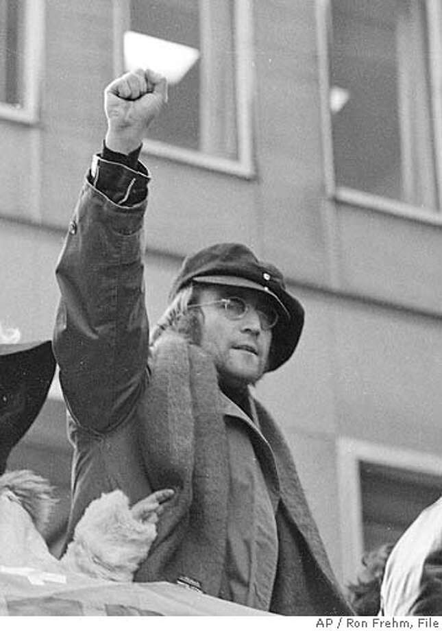 "** FILE ** John Lennon and his wife Yoko Ono raise their fists as they join a protest in this Feb. 5, 1972, file photo in front of British Overseas Airways Corp. offices in New York on Fifth Avenue. The demonstrators called for the withdrawal of British troops from Northern Ireland. The documentary, ""The U.S. vs. John Lennon,"" which is being premiered at the Toronto Film Festival, examines the former Beatle's deportation battle with the Nixon administration, which had him under surveillance over his anti-war activities. (AP Photo/Ron Frehm, File) A FEB 5 1972 B&W FILE PHOTO Photo: RON FREHM"