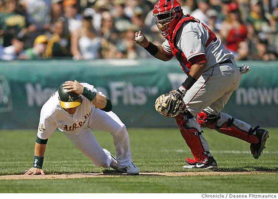 Marco Scutaro is caught in a rundown by Jose Molina. Oakland Athletics play Los Angeles Angels at McAfee Coliseum in Oakland on 9/23/06.  (Deanne Fitzmaurice/ The Chronicle) Photo: Deanne Fitzmaurice