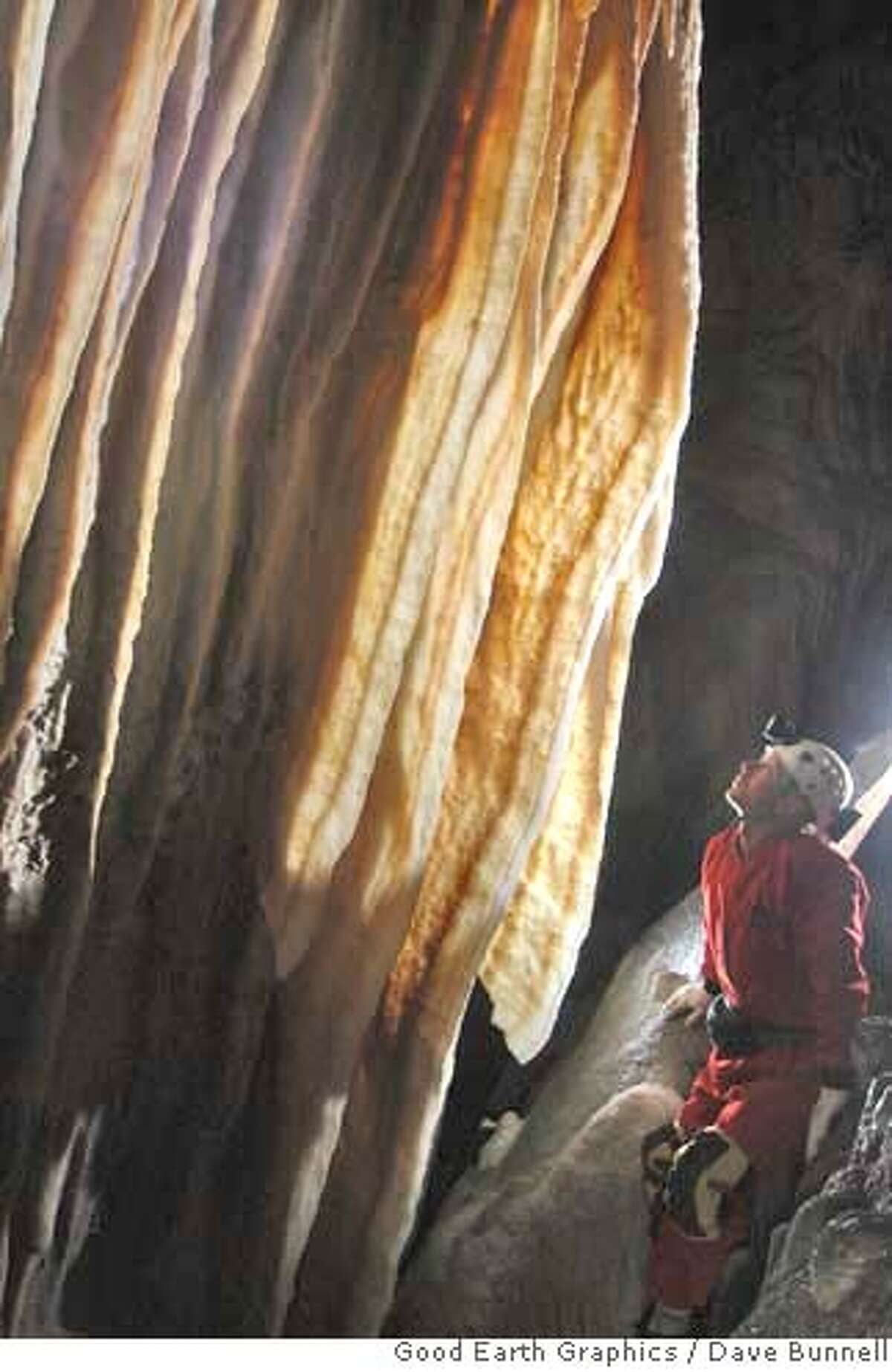 Scott McBride, a cave explorer from San Andreas, examines a cave curtain deep within Ursa Minor, the cave he discovered at Sequoia and Kings Canyon National Parks. The cave extends more than 1,000 feet and features five rooms and several passages. PHOTO BY DAVE BUNNELL, GOOD EARTH GRAPHICS