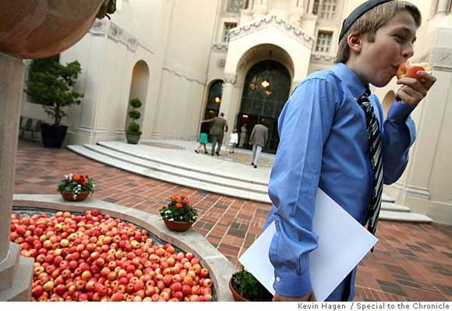 Samuel Stone, 13, takes a bite from an organic gala apple from the courtyard fountain at Temple Emanu-El in San Francisco. The temple replaced the water in the fountain with apples in honor of Rosh Hashana, the beginning of the Jewish new year. Apples dipped in honey signify a sweet beginning to the new year. By KEVIN HAGEN/SPECIAL TO THE CHRONICLE Photo: KEVIN HAGEN