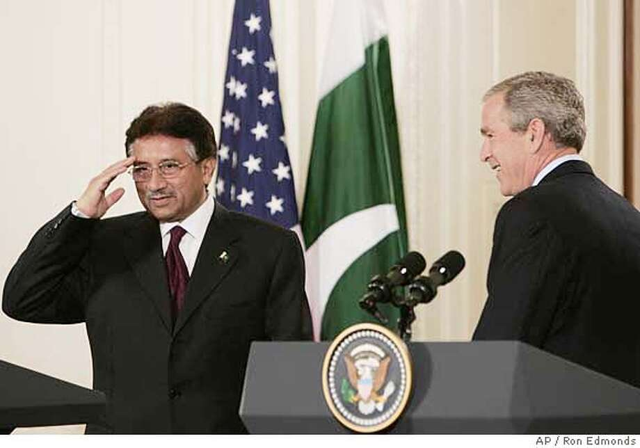 "President Bush looks on as Pakistan President Gen. Pervez Musharraf salutes, Friday, Sept. 22, 2006, as they finished their joint news conference in the East Room at the White House in Washington. President Bush said Friday he was ""taken aback"" by a purported U.S. threat to bomb Pakistan back to the Stone Age if it did not cooperate in the fight against terrorism after the Sept. 11 attacks. He praised Musharraf for being one of the first foreign leaders to come out after the Sept. 11, 2001, attacks to stand with the U.S. to ""help root out an enemy."" (AP Photo/Ron Edmonds) Photo: RON EDMONDS"