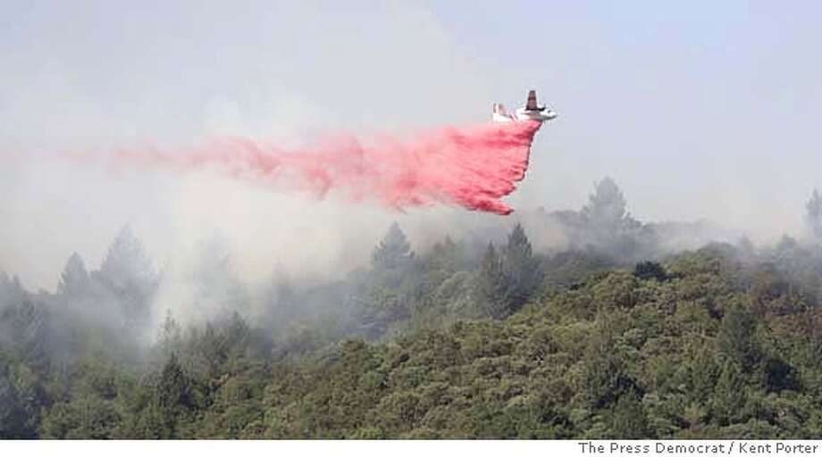 A California Department of Forestry air tanker drops retardant above the Yountville Veterans home Friday, Sept. 22, 2006, near Yountville, Calif. More than 100 firefighters, air tankers and inmate crews also were fighting a fire near Yountville in Napa County, about an hour north of San Francisco. Officials said they did not yet know the size of that fire. (AP Photo/The Press Democrat, Kent Porter) ** MAGS OUT ** MAGS OUT Photo: KENT PORTER