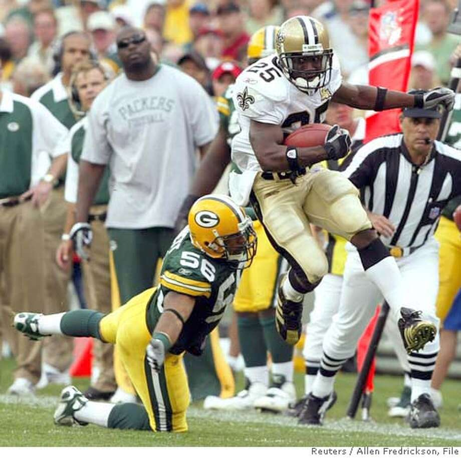 New Orleans Saints running back Reggie Bush (25) eludes Green Bay Packers linebacker Nick Barnett (56) as he picks up 23 yards on a third quarter pass play during their NFL game in Green Bay, Wisconsin September 17, 2006. REUTERS/Allen Fredrickson (UNITED STATES) Photo: ALLEN FREDRICKSON
