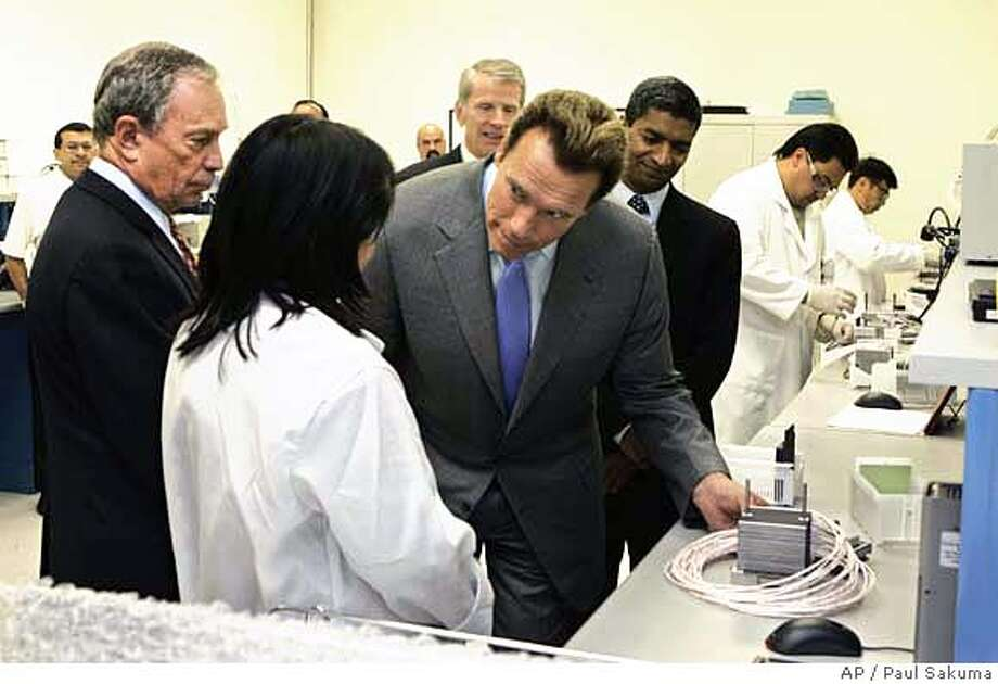Calif. Gov. Arnold Schwarzenegger, center, and New York City Mayor Michael Bloomberg, far left, listen to Bloom Energy technician Mariline Abriam, second from left, in a lab at Bloom Energy Corp. in Sunnyvale, Calif., Thursday, Sept. 21, 2006. Bloom Energy produces electricity using fuel cell technology by Bloom Energy. (AP Photo/Paul Sakuma) Photo: PAUL SAKUMA