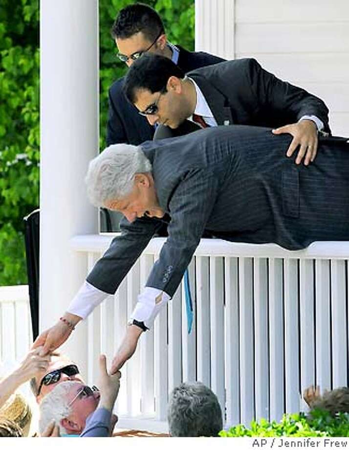 While a Secret Service agent holds onto his waist, former President Bill Clinton stretches over a porch rail and shakes hands with well-wishers during a campaign stop on Sunday, May 4, 2008, in Morganton, N.C. The former president was campaigning for his wife, Democratic presidential hopeful, Sen. Hillary Rodham Clinton, D-N.Y. (AP Photo/The News Herald,Jennifer Frew) Photo: Jennifer Frew