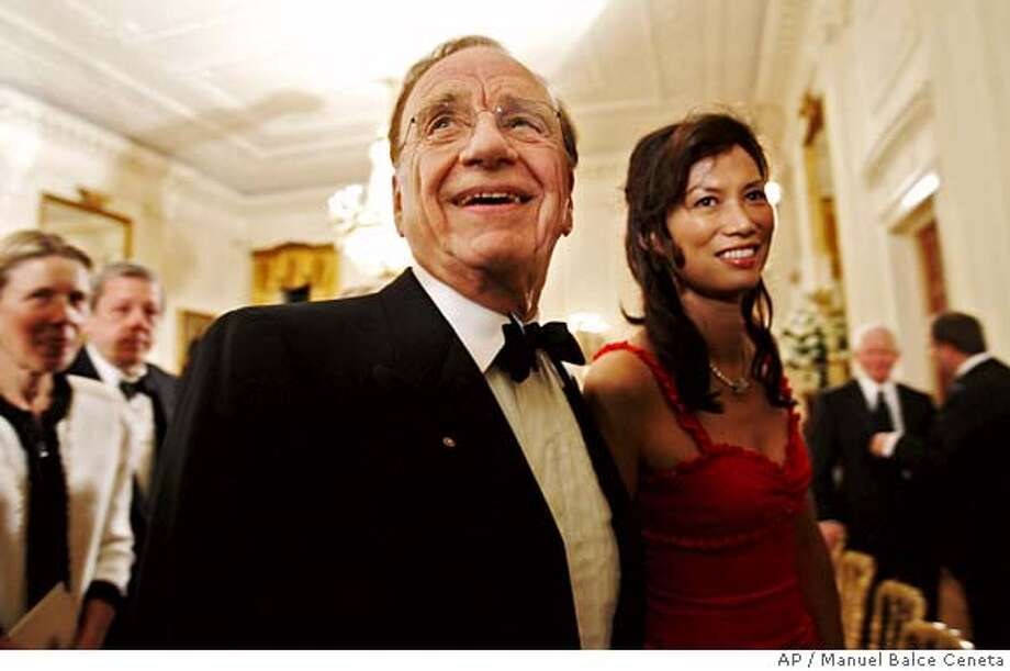 Media mogul Rupert Murdoch and his wife Wendi Deng leave the East Room at the conclusion of an entertainment portion of a reception hosted by President Bush and first lady Laura Bush for visiting Australian Prime Minister John Howard and his wife Janette Howard at the White House, Tuesday, May 16, 2006 in Washington. (AP Photo/Manuel Balce Ceneta) Photo: MANUEL BALCE CENETA