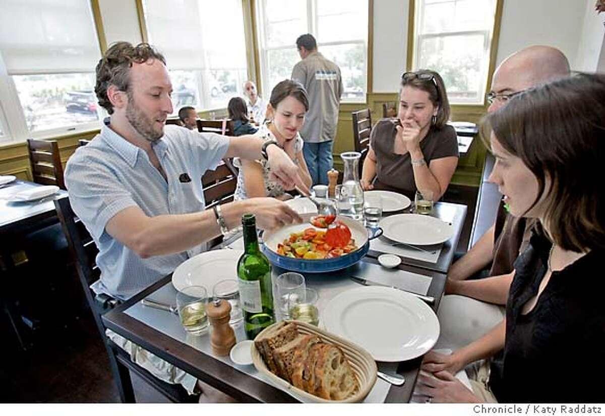 Family style: Joe Burton serves heirloom tomato salad to Sarah Burton (left), Carly Guthrie, Matthew Kenaston, Margot Kenaston (right). Chronicle photo by Katy Raddatz