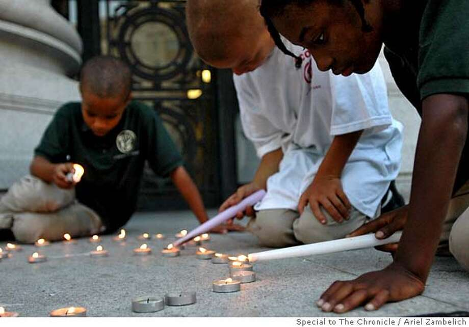 (right to left) Siblings Natasha, 8, Gabriel, and Dazjon Brown, both 9, light candles at a vigil on the steps of City Hall in Oakland on Tuesday night. The Association for Community Organizations for Reform Now (ACORN) held the vigil in honor of the 108 homicides in Oakland this year so far in hopes of raising awareness of violence in the city. Ariel Zambelich/Special to The Chronicle Photo: Ariel Zambelich
