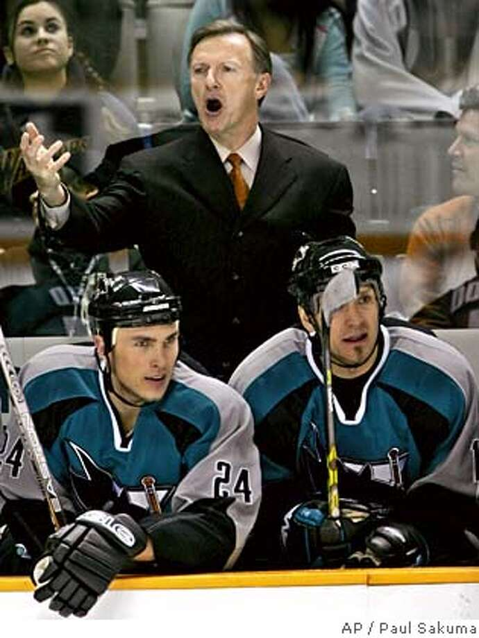 San Jose Sharks head coach Ron Wilson, upper, gestures as Sharks left wing Josh Langfeld, left, and left wing Scott Thornton, right, watch the game against the Atlanta Thrashers in the second period, Tuesday, Dec. 6, 2005 in San Jose, Calif. (AP Photo/Paul Sakuma) Ran on: 12-16-2005  Sharks coach Ron Wilson can get back to barking commands at his players after a long layoff. Photo: PAUL SAKUMA