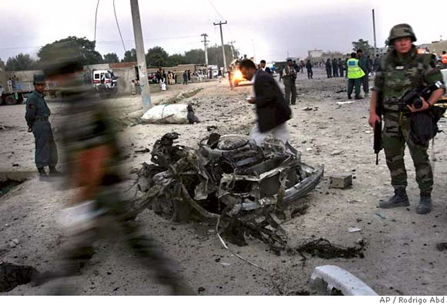 French soldiers arrive to the scene where a car bomber killed three Afghan police and wounded five people in Kabul, Afghanistan, Monday, Sept. 18, 2006. A suicide car bomber killed three Afghan police and wounded five other people in Kabul on Monday, an official said. (AP Photo/Rodrigo Abd) Photo: RODRIGO ABD