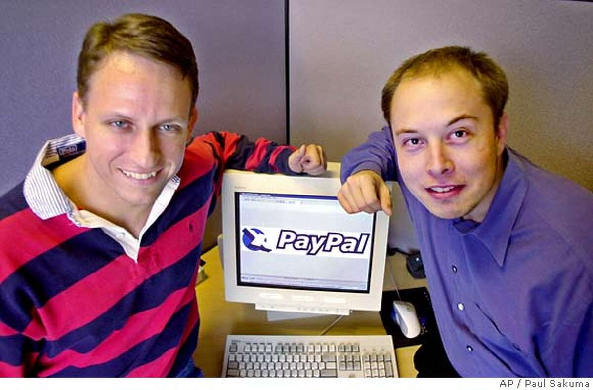 FILE--PayPal Chief Executive Officer Peter Thiel, left, and founder Elon Musk, right, pose with the PayPal logo at corporate headquarters in Palo Alto, Calif., on Oct. 20, 2000. Online auction giant eBay Inc. announced Monday, July 8, 2002, it is buying the electronic payment facilitator for more than $1.3 billion in stock, in a long-rumored deal the companies hope will make Internet trading faster, easier and safer. (AP Photo/Paul Sakuma, File)Ran on: 04-12-2006 San Joses PayPal says it is evaluating it legal options. Ran on: 07-13-2006 Benioff CAT OCT 20 2000 FILE PHOTO