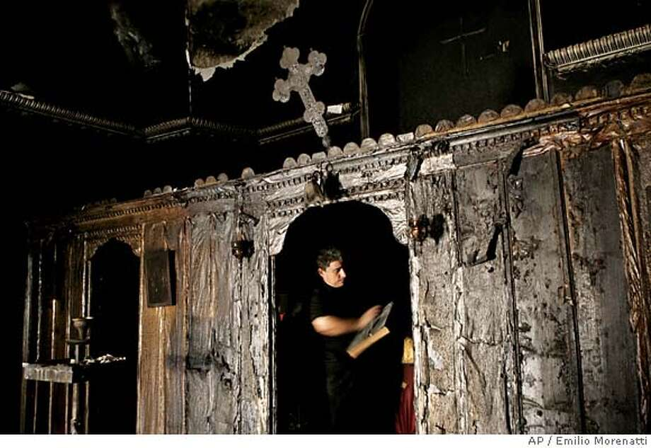 Palestinian Greek Orthodox worshiper, Samir Mitri, cleans a holy book as he inspects the damage in the burned Greek Orthodox church in the West Bank town of Tulkarem, Sunday Sept.17 2006. The stone church built 170 years ago was torched before dawn and its entire inside was destroyed, local Christian officials said. The church is one of two West Bank churches that were set afire early Sunday as a wave of Muslim anger over comments by Pope Benedict XVI construed as anti-Islam grew throughout the Palestinian areas. (AP Photo/Emilio Morenatti) Photo: EMILIO MORENATTI