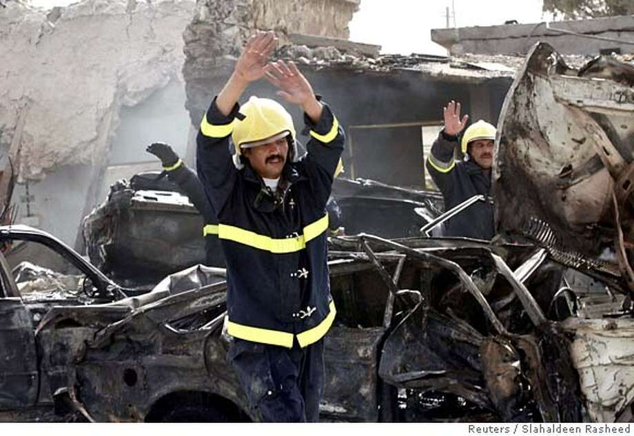 Firemen gesture at the scene of a suicide truck bomb attack outside the offices of the Patriotic Union of Kurdistan (PUK), the political party of Iraq's President Jalal Talabani, in Kirkuk, about 250 km (150 miles) north of Baghdad, September 17, 2006. Four blasts killed 23 people in Iraq's ethnically mixed city of Kirkuk on Sunday, including a huge suicide truck bomb, a day after Prime Minister Nuri al-Maliki urged divided Iraqis to embrace reconciliation. REUTERS/Slahaldeen Rasheed (IRAQ) 0 Photo: SLAHALDEEN RASHEED