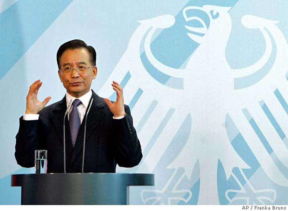 Chinese Prime Minister Wen Jiabao answers questions during a press conference with German Chancellor Angela Merkel, unseen, in the Chancellory in Berlin, Thursday, Sept. 14, 2006. Chinese Prime Minister Wen Jiabao on Thursday reiterated his opposition to imposing sanctions against Iran, saying a solution to the standoff over Tehran's nuclear program could still be reached through peaceful efforts. In background is an image of the German federal eagle. (AP Photo/Franka Bruns) Photo: FRANKA BRUNS