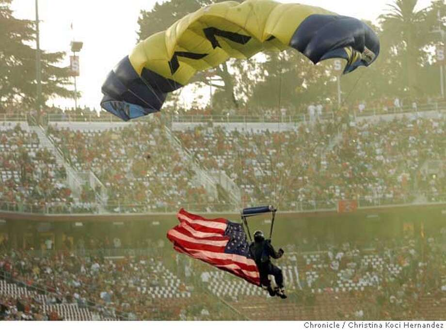 Navy parachute jumpers land in the new stadium, this one carrying the American flag.Unveiling of newly rebuilt Stanford Stadium, for the football team's home opener against Navy.  New stadium holds 35,000 fewer people but has more and better food, luxury boxes, and the seats are closer to the field (no track). . (CHRISTINA KOCI HERNANDEZ/THE CHRONICLE) Mandatory Credit For and San Francisco Chronicle/No-Sales-Mags Out Photo: Christina Koci Hernandez