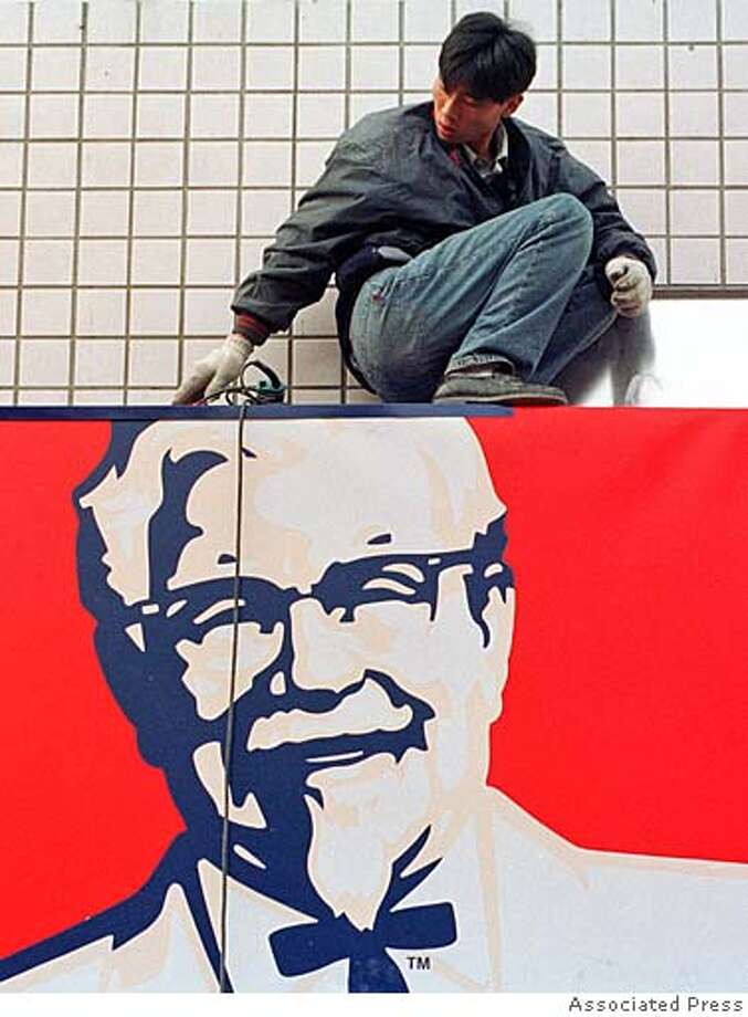 A Chinese worker installs a new billboard outside a Kentucky Fried Chicken restaurant in Beijing Tuesday, Nov. 23, 1999. China's likely entry into the World Trade Organisation is expected to provide a boost to its economy with increased foreign investment. However millions are also expected to lose their jobs, a result of increased competition from higher quality foreign products. (AP Photo) Photo: Associated Press