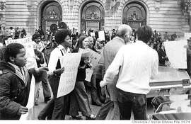 ZEBRAMURDER-22APR1974-SE - Mayor Joe Alioto, on his way to his card outside of City Hall. Protesters of the Zebra Murders, holding signs, follow him. Photo by Susan Ehmer