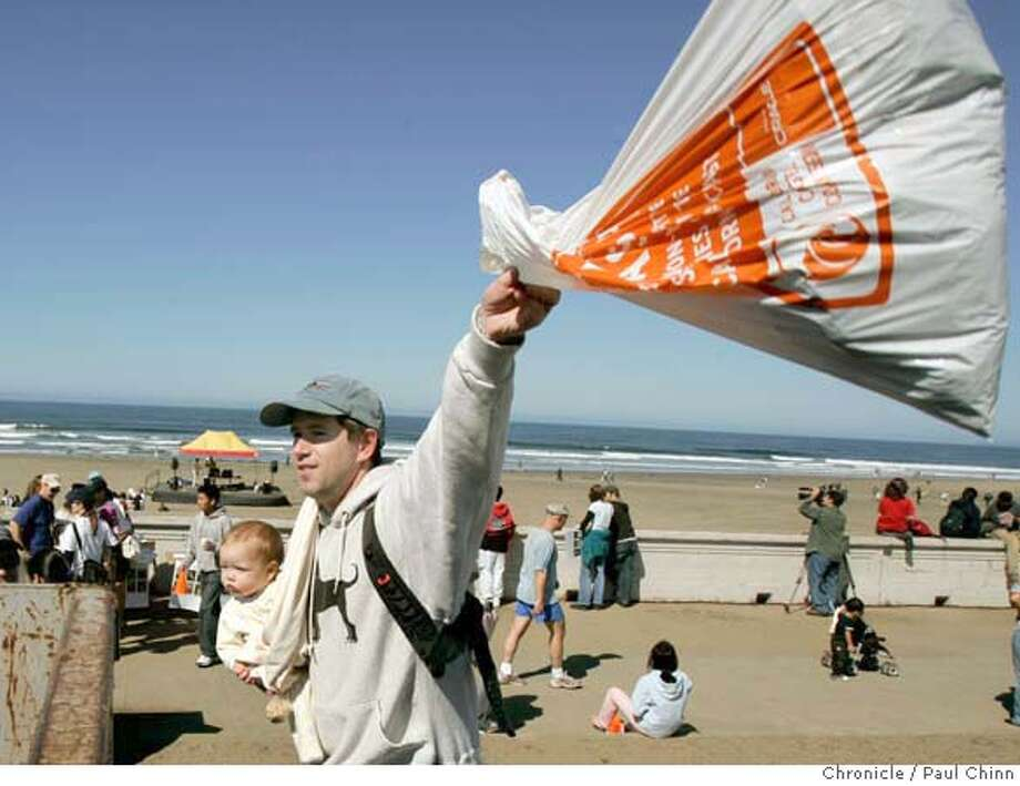 Holding his daughter Charlotte, Tom Fishburne of Alameda tosses a bag of trash he collected into a dumpster during the annual California Coastal Cleanup at Ocean Beach in San Francisco, Calif. on Saturday, September 16, 2006. About 500 volunteers roamed the beach to pick up trash and debris. PAUL CHINN/The Chronicle  **Tom Fishburne, Charlotte MANDATORY CREDIT FOR PHOTOGRAPHER AND S.F. CHRONICLE/ - MAGS OUT Photo: PAUL CHINN