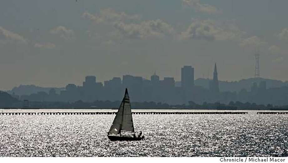 standalone_025_mac.jpg A lone sailboat passes across the SF Skyline heading to the Berkeley Marina. Standalone nice afternoon weather around San Francisco Bay. From Cesar Chavez Park at the Berkeley Marina. 10/28/04 Berkeley, CA Michael Macor / San Francisco Chronicle Ran on: 10-30-2004  Photo caption Mandatory Credit for Photographer and San Francisco Chronicle/ - Magazine Out Photo: Michael Macor