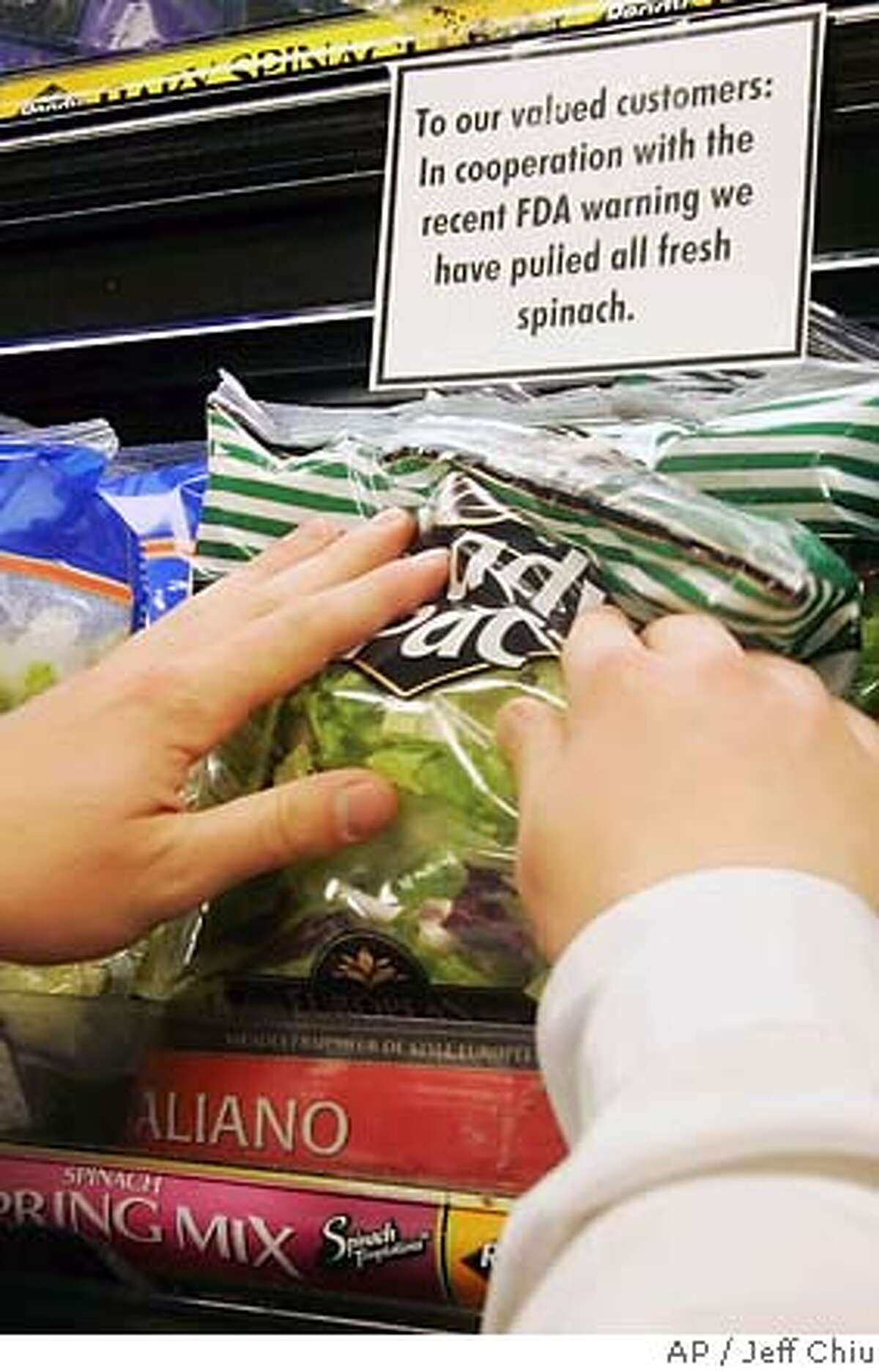 A sign informing customers that fresh spinach has been removed is shown as produce worker Pete Kettell stocks packaged salad mixes at Mollie Stone's Tower Market in San Francisco, Friday, Sept. 15, 2006. With at least one dead and dozens sickened across 10 states, health officials focused on California as the likely source of spinach contaminated by E. coli as grocers cleared the vegetable from their shelves. (AP Photo/Jeff Chiu)