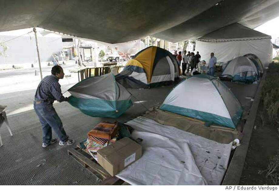 A supporter of Mexican presidential candidate Andres Manuel Lopez Obrador, who narrowly lost the election to conservative Felipe Calderon, begins to pull down tents that have clogged up the heart of Mexico City for more than six weeks in protest against alleged fraud in the July presidential election on Sept. 14, 2006. Lopez Obrador has promised that the entire tent city will be cleared by Saturday, so that the army can conduct its annual parade to celebrate Mexico's independence.(AP Photo/Eduardo Verdugo) Photo: EDUARDO VERDUGO