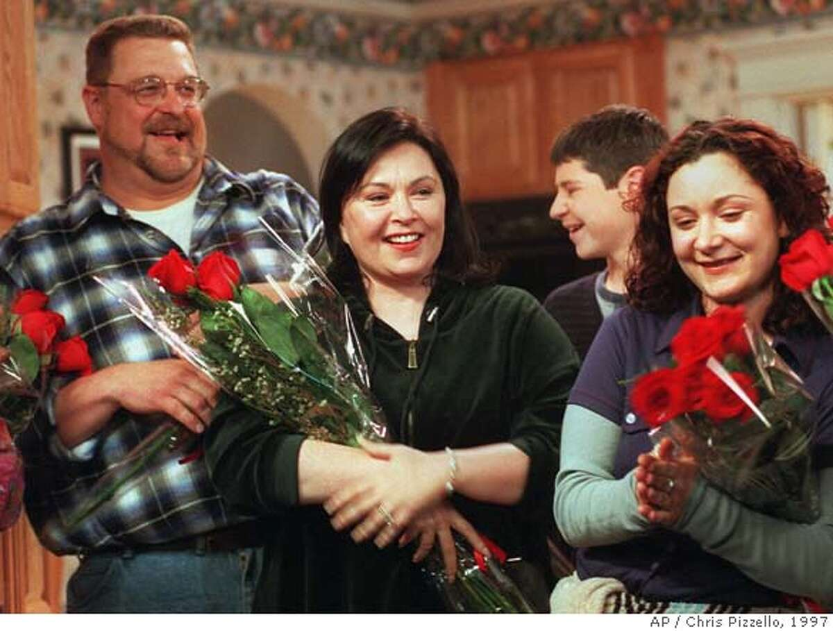 """Comedienne/actress Roseanne, center, star of the longtime ABC sitcom """"Roseanne,"""" basks in applause with co-stars John Goodman, left, and Sara Gilbert after taping was completed on the 221st and final episode of the show, Friday, April 4, 1997, at Radford Studios in Los Angeles. The final episode is scheduled for May 20. Goodman plays Roseanne's husband on the show and Gilbert her daughter.Roseanne's Conner clan, who replaced Bill Cosby's Huxtables as America's favorite television family only to fade from prominence this year, is finally saying goodbye. (AP Photo/Chris Pizzello) STAND ALONE PHOTO"""