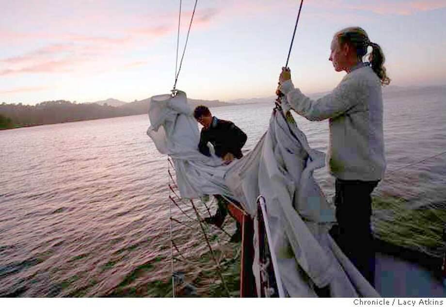 (left to right) As the sunsets Aaron Koch and Anita Kasch take in the jib for the night, Wednesday, Aug. 23, 2006, behind Tiburon, Ca. (Lacy Atkins/The Chronicle) Photo: Lacy Atkins