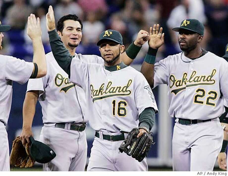 Oakland Athletics' Eric Chavez, left, Jay Payton (16) and Milton Bradley (22) celebrate a 1-0 victory over the MInnesota Twins in Minneapolis, Wednesday, Sept. 13, 2006. (AP Photo/Andy King) Photo: ANDY KING