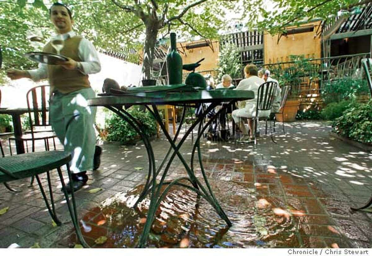A water feature is designed as a cafe table in the outdoor patio of Ristorante Tra Vigne in St. Helena.