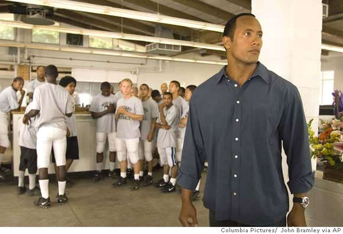 In this photo provided by Columbia Pictures, teenagers at a juvenile detention center, under the leadership of their counselor (Dwayne Johnson), gain self-esteem by playing football together in