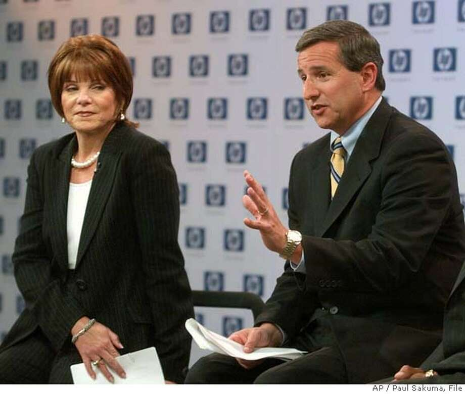 """** FILE **Hewlett-Packard Co. president and CEO Mark Hurd, center, gestures as he sits next to Patricia Dunn, left, HP's non-executive chairman, during a news conference at HP headquarters in a Palo Alto, Calif. file photo from March 30, 2005. Dunn is stepping down in January, felled by what she admitted were """"inappropriate techniques"""" to probe boardroom leaks to the media. Hurd, who has the respect of Wall Street and is untainted by the """"pretexting"""" scandal at the computer and printer maker, will take over, vowing that the investigation's methods """"have no place in HP."""" (AP Photo/Paul Sakuma, File) MARCH 30, 2005 FILE PHOTO Photo: PAUL SAKUMA"""